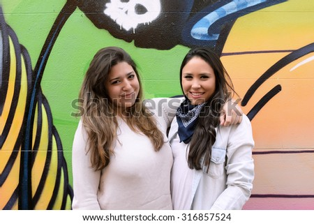 Two young hispanic women posing against a colorful wall. Urban style. - stock photo