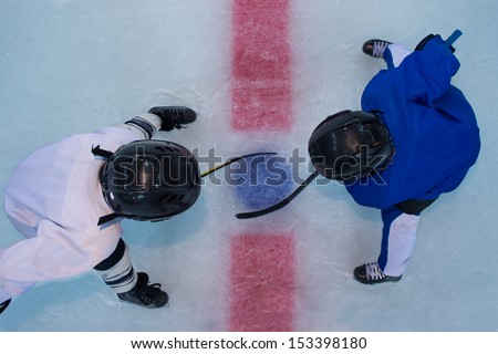 Two young hockey players stands on red line in face off. Top view - stock photo