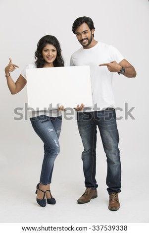 Two young Indian people pointing a blank billboard white background - stock photo