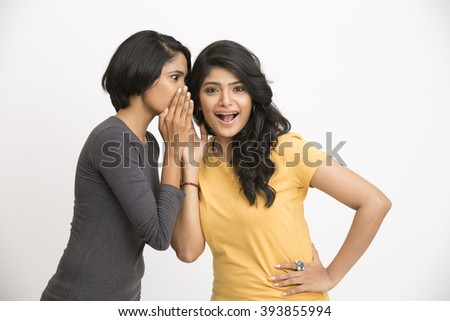 two young Indian women gossiping on white background. - stock photo