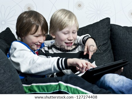 Two young kids in a sofa having fun together with a tablet - stock photo