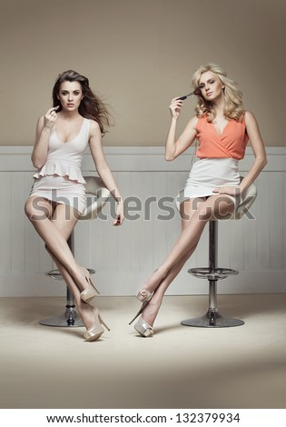 Two young ladies doing make up - stock photo
