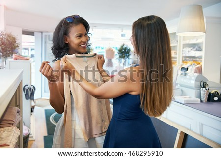 Two young ladies shopping for clothes together in a fashion boutique choosing a long sleeved top holding it up with a smile