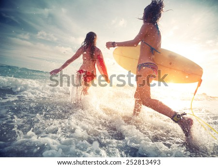 Two young ladies surfers running into the sea with surf boards