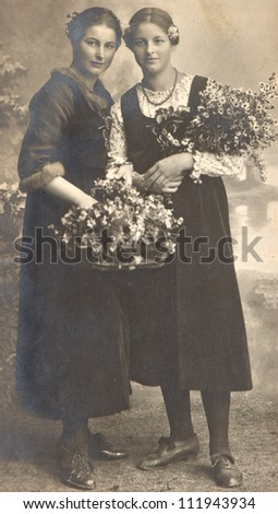 two young ladies with flowers. vintage picture ca. 1920 - stock photo