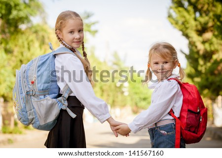 two young little girls preparing to walk to school - stock photo