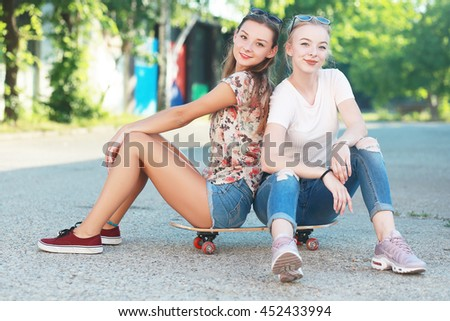 Two young longboarding girl friends sitting together on long-board and having fun. Outdoors - stock photo