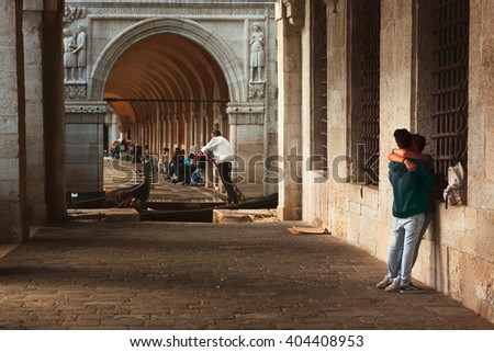 Two young lovers hug and watch gondolier in typical venetian gallery.