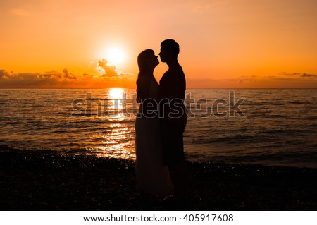 Two young lovers standing on a beach and looking to each other on sunset