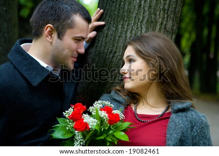 Two young lovers talking to each other in park