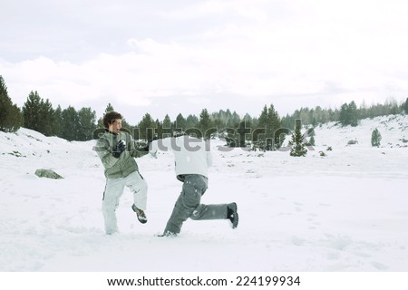 Two young male friends roughhousing in snow, full length - stock photo