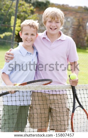Two young male friends with rackets on tennis court smiling - stock photo