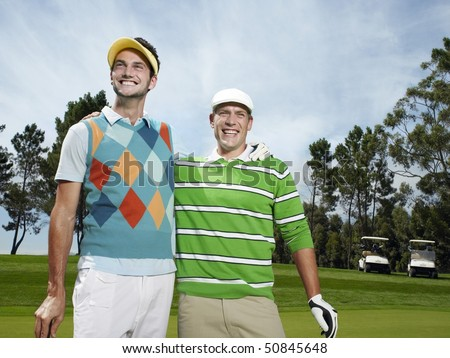 Two young male golfers on green - stock photo