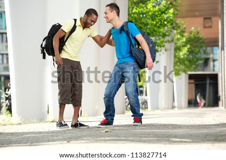 Two young male students walking and laughing outdoors on college campus. Full length portrait of a young African American male student with Caucasian student - stock photo