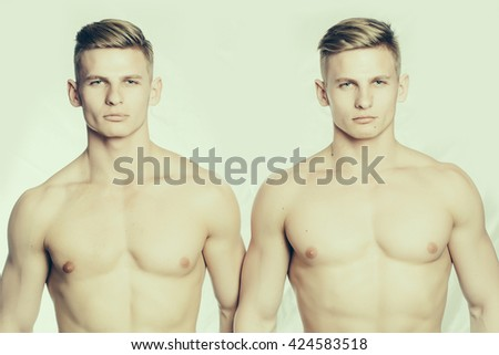 Two young male twins with sexy body and muscular chest stand together on white background