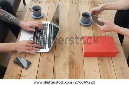 two young man using laptop and a smartphone.focus on the hand - stock photo