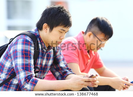 Two young man using mobile phone