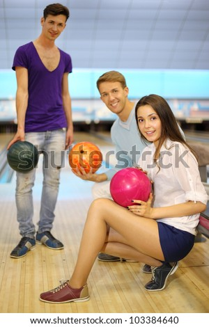 Two young men and girl with balls in bowling club; left man stands and others sit; shallow depth of field; focus on woman - stock photo