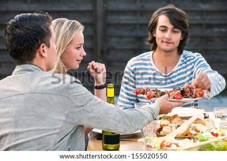 Two young men and woman enjoying a dinner party outside - stock photo