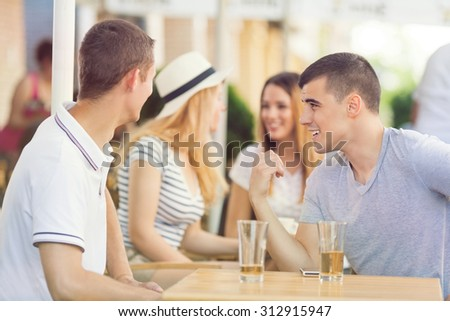 Two young men are sitting in a cafe looking at two beautiful girls in the background. One of them is pointing to the girls and talking about them to  his friend.