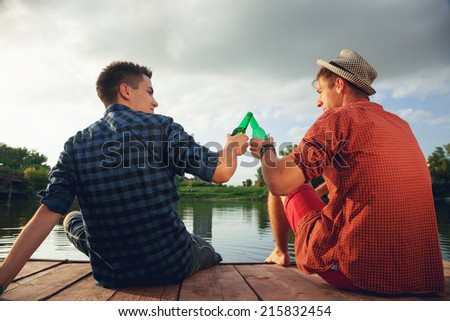 Two Young Men Enjoying Beside River And Drinking Beer - stock photo
