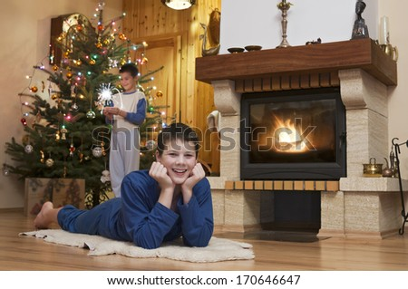 Two young men front of fireplace with Christmas tree in background