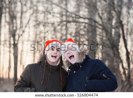 Two young men in Christmas hats Santa Claus