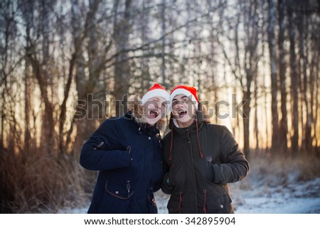 Two young men in Christmas hats Santa Claus - stock photo