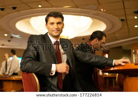 Two young men in suits behind gambling table in a casino - stock photo