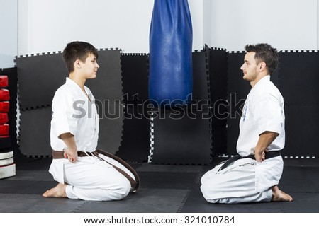 Two young men in white kimono down on their knees ready to start fighting in the gym - stock photo