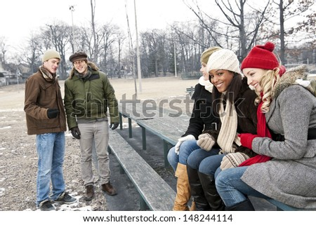 Two young men looking at three pretty women in winter park - stock photo