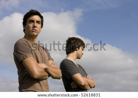 Two young men looking on opposite sides