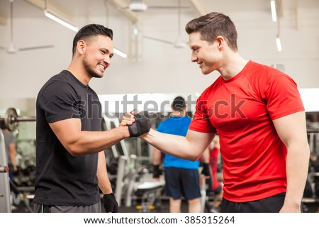 Two young men meeting at the gym and giving each other a handshake - stock photo