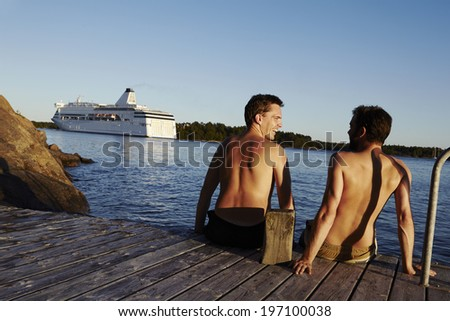 Two young men on jetty, Sweden - stock photo
