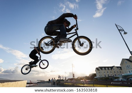 Two Young men performs BMX stunts during sunset at the street.