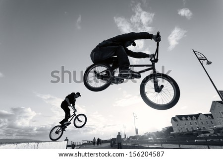 Two Young men performs BMX stunts during sunset at the street. Monochromatic