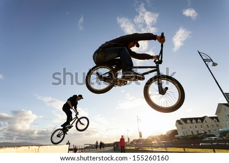 Two Young men performs  stunts during sunset at the street. - stock photo