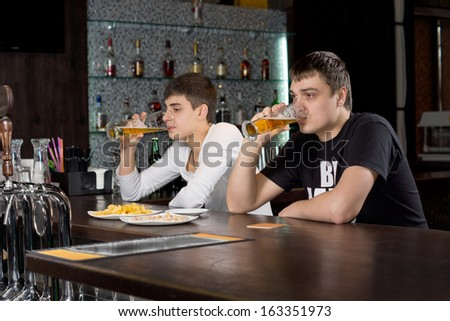 Two young men relaxing at the bar sitting at the counter together drinking beer