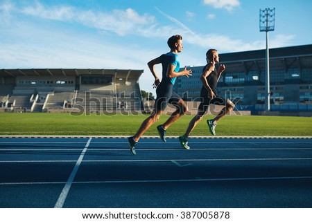 Two young men running on race track. Male professional athletes running on athletics race track. - stock photo