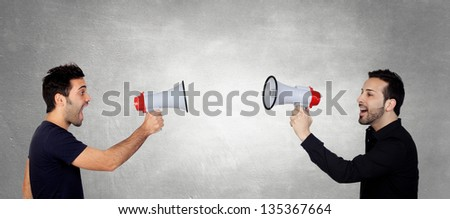 Two Young Men Shouting Through Megaphone In Front Of Each Other - stock photo
