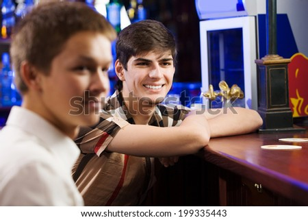 Two young men sitting at bar and talking