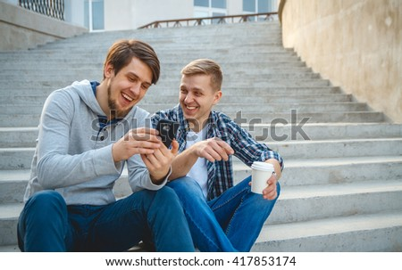 Two young men sitting on the steps and laughing, looking at the phone - stock photo
