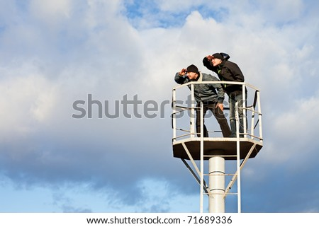 Two young men standing on tower against sky. Looking into distance - stock photo