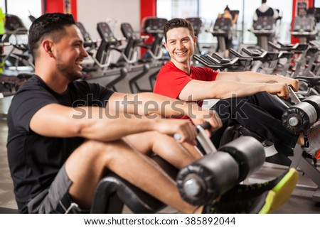 Two young men taking a break between exercises and talking to each other after doing some crunches in a gym  - stock photo