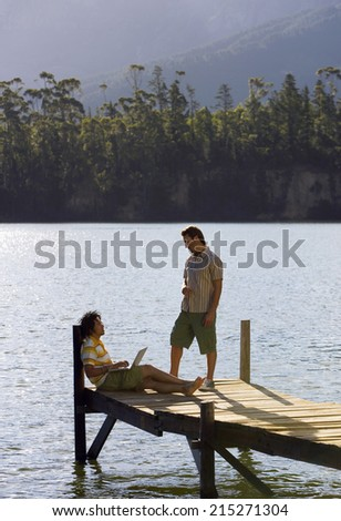 Two young men talking on lake jetty, man leaning against wooden post, using laptop, profile - stock photo