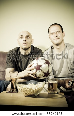 Two young men watching a football match on tv. Sport fans