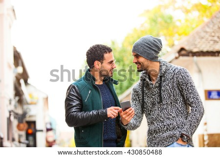 Two young men with a smart phone standing outside, both looking at the screen - stock photo