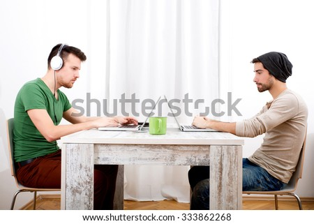 Two young men working in their home office