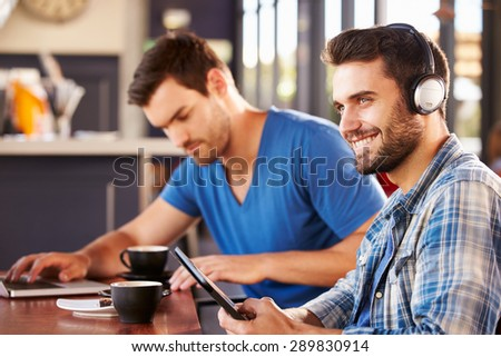 Two young men working on computers at a coffee shop - stock photo