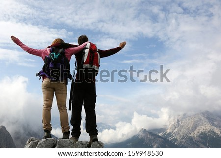 Two young mountaineers standing on mountain top and enjoying their success - stock photo
